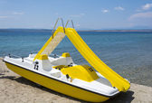 Yellow pedal boat on a beach — ストック写真