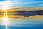 The melting iceberg on spring mountain lake in the setting sun. — Stock Photo