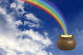 Pot with gold at the basis of a rainbow — Stock Photo