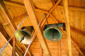 Tow brass bells under wooden roof — Stock Photo