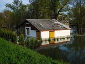 Flooded house on a river bank — Stock Photo
