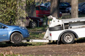 Truck towing car parked wrongly off parking lot — Stock Photo