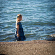 The little girl in a blue dress on the sea. — Stock Photo