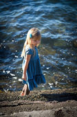 The little girl in a blue dress on the sea. — Стоковое фото