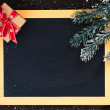Blackboard decorated with fir branch and a gift box. — Stock Photo