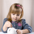 Stock Photo: Child putting coin into piggy bank.