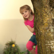 Little girl peeking out from behind a tree. — Stock Photo