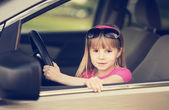 Little girl driving a car. — Foto Stock