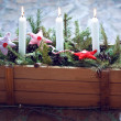 Christmas decoration: Burning candles in a wooden box with fir branches and Christmas fabric toys — Stock Photo