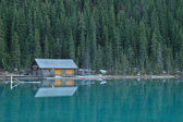 Little cottage near pristine lake — Stock Photo