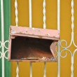 Stock Photo: Rusty red broken letterbox hanged on fence