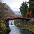 Stock Photo: Ancient Japanese red arc bridge crossing creek surrounded by Aut