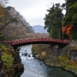 Ancient Japanese red arc bridge crossing creek surrounded by Aut — Stock Photo