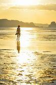 Girl walking on the beach on sunset — Stock Photo
