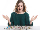 Young happy woman raising her hands in front of a table with many rings lying — Stock Photo