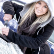 Stock Photo: Young womscraping ice from car