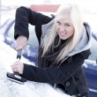 Stock Photo: Young unhappy womscraping ice from car