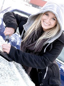 Young woman scraping ice from car — Stok fotoğraf