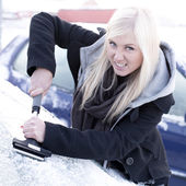 Young unhappy woman scraping ice from car — Stockfoto