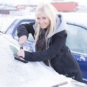 Smiling young woman scraping ice from car window — Stock Photo