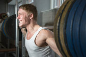 Young man using smith machine — Stock Photo