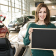 Young brunette holding blackboard inside car dealership — Stock Photo