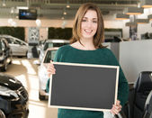 Young brunette holding blackboard inside car dealership — Stock Photo