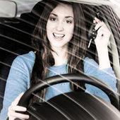 Young brunette holding car key inside car dealership — Stock Photo