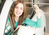 Woman holding car key inside car dealership — Foto Stock