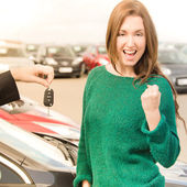 Excited woman receiving key for car — Stock Photo