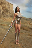 Girl in a chain armour with a sword — Stock Photo