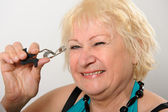 Woman using eyelash curler. — Stock Photo