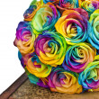 Rainbow roses bouquet on box — Stock Photo