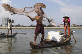 Fisherman on a wooden barge throwing a fishing net on the river — Stock Photo