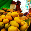 Stack of fresh mangos at market stall, tropical fruit — Stock Photo #37420601