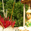 Red incense sticks in front of buddhist statue — Stock Photo #37506157