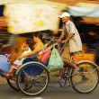 Rickshaw bicycle with passengers driving by, old man cycling — Stock Photo