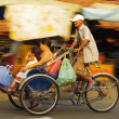 Rickshaw bicycle with passengers driving by, old man cycling — Stock Photo #37507837