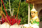 Red incense sticks in front of a buddhist statue — Stock Photo