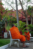 Buddhist monk in Cambodia sitting on a bench in a garden — Stock Photo