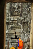 Buddhist monks in Angkor Wat, Cambodia, in front of a stone carv — Stock Photo