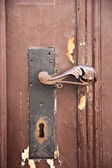Aged door handle of a wooden door — Stock Photo