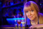 Blond girl with 3 flaming drinks resembling Russian Flag — Stock Photo