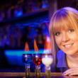 Smiling blond girl with 3 flaming drinks in colors representing the Russian Flag — Stock Photo