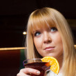 Stock Photo: Lonely young lady enjoying drink in bar