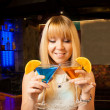 Stock Photo: Smart blond girl gets 2 drinks for 1 price in club and smiles