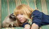 Pretty blond girl with a cat relaxing on sofa — Stock Photo