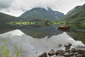 Wooden boat floating in a norwegian fiord — Stock Photo