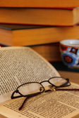 Reading a book in a library with eyeglasses and a cup of espresso. — Foto de Stock