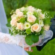 Wedding theme, hands and rings on wedding bouquet — Stock Photo